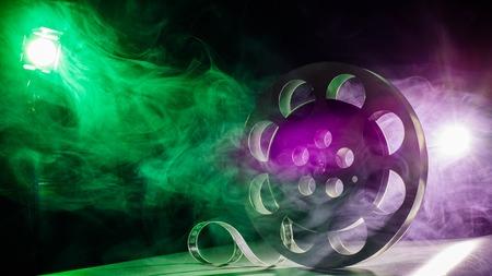 cinta pelicula: Carrete de la película de la película en la retro en el humo de color verde y púrpura sobre un fondo oscuro Foto de archivo
