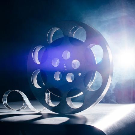 rollo pelicula: Carrete de la película de la película en la retro en el humo azul sobre un fondo oscuro Foto de archivo