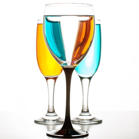one glass of wine and two champagne on a white background
