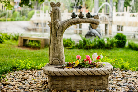 animal figurines: stone figurines of birds sitting on a branch,summer evening Stock Photo