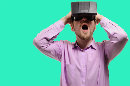 ber: surprised man with glasses of virtual reality in a lilac shirt on green background.