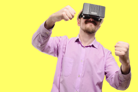 nice man with glasses of virtual reality in a lilac shirt on yellow background.
