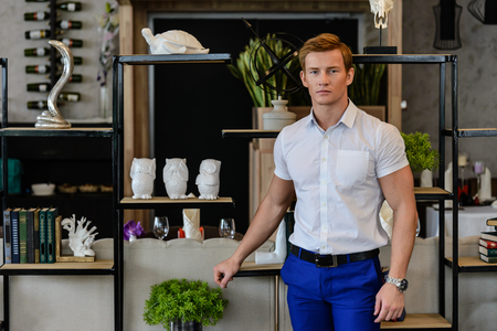 in vouge: Young sporty man in white shirt and blue pants standing at home near books
