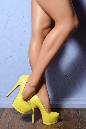 shapely legs: Beautiful shapely female legs in yellow shoes leather reptile on wooden flour Stock Photo