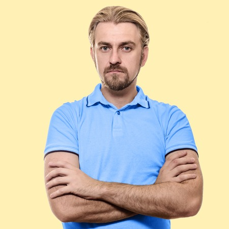 in vouge: Stylish young man standing arms crossed in a blue T-shirt isolated on a yellow background