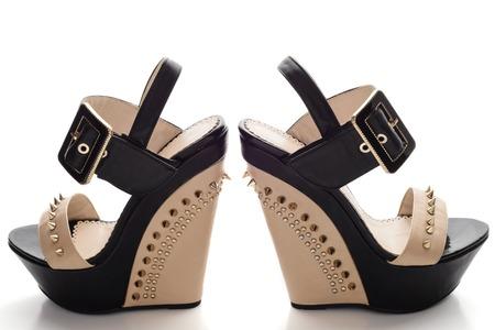 pies sexis: Femeninos zapatos de plataforma de color negro con inserciones de color beige y clavos aislados en blanco Foto de archivo