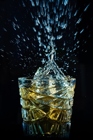 falling cubes: whiskey splash from the falling ice cubes in faceted crystal glass isolated on a black background