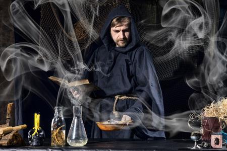 Halloween-Magier bereitet sich für ein magisches Ritual in der alten Tabelle vor Standard-Bild - 64150018