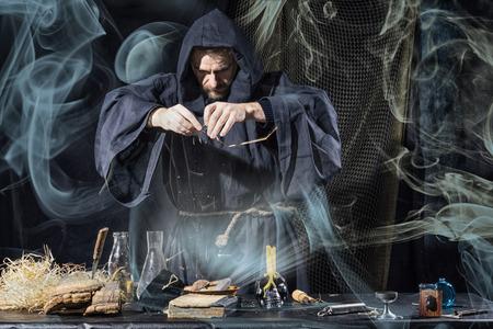Halloween. Der mittelalterliche Alchimist hält in seinem Labor Rauch am Tisch magisches Ritual im Hintergrund Standard-Bild