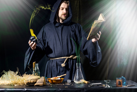 conducts: Halloween. The medieval alchemist conducts holding a skull with candle reading a book at the table in his laboratory in the smoke