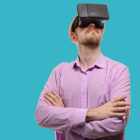 nice man with glasses of virtual reality in a lilac shirt on blue background.