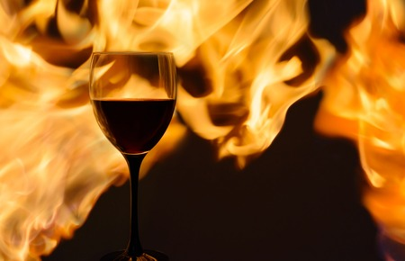 glass of wine in the flame. horizontal. Selective focus, golden glow from the fire.