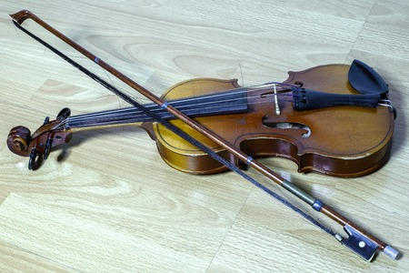 vintage violin with a bow lies on a wooden bench