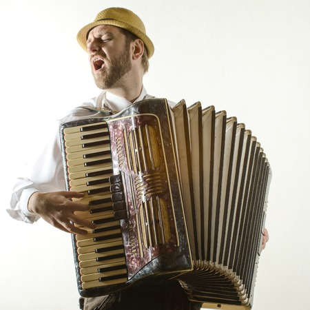 Portrait of professional musician with accordion at white wall Stock Photo