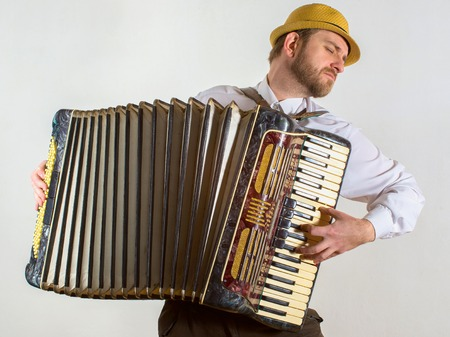 Portrait of a man in straw hat playing on accordion.