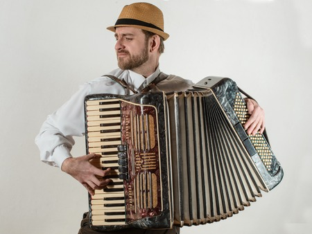 The musician playing the accordion on white background Stock Photo