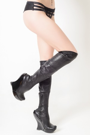 Shapely female legs in fashionable high black leather boots.