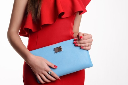 Close up fashion woman in red dress with blue handbag. Stock Photo