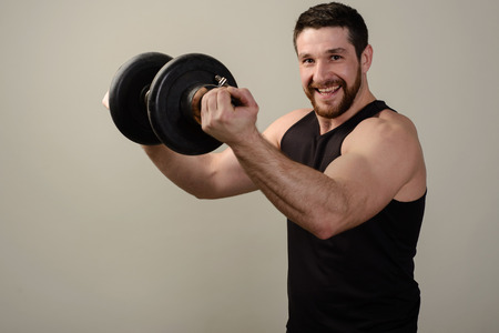 A smiling young bearded athlete in a black T-shirt raises a heavy dumbbell in front of him.