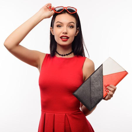 Surprised slender young woman in a red dress and clutch holds on to sunglasses in the shape of a heart.