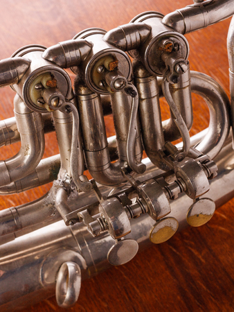 saxhorn: Part of the valve mechanism of an old tenorhorn on a wooden background