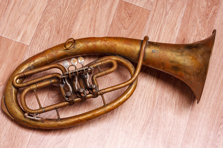 saxhorn: old rusty alto saxhorn on wooden background. Stock Photo