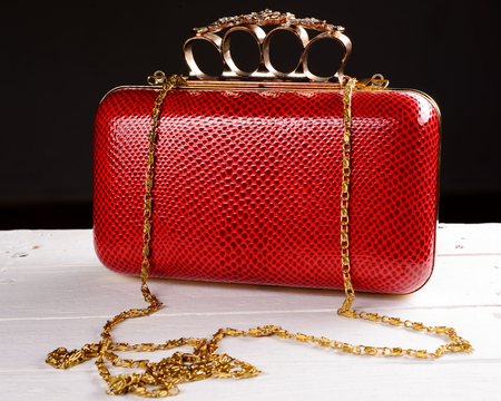 Red hand bag clutch with pen brass knuckle on black background. Stock Photo