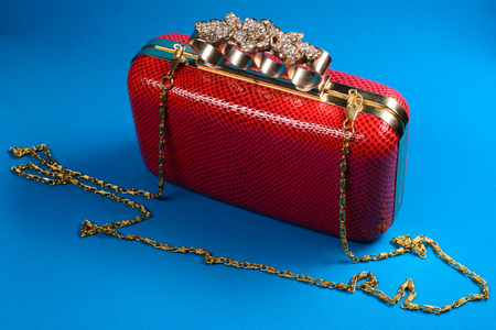 Red handbag clutch with chain on blue background. Stock Photo