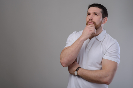Puzzled young man stroking touching beard looking at camera over gray background.
