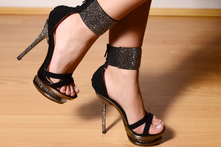 girl in a chic black sandals with high heels standing on a wooden floor.