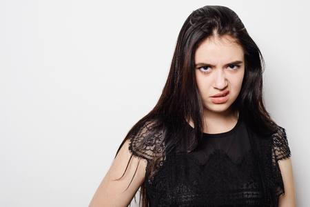 Closeup portrait, pangry, grumpy, skeptical young woman with bad attitude, looking at you isolated grey background. Negative human emotion, facial expressions, feelings Banque d'images