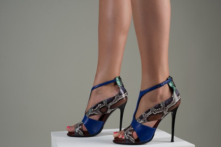 Beautiful female feet in stylish blue high-heeled sandals. Stock Photo