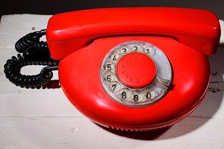 Red vintage phone on white wooden background Stock Photo