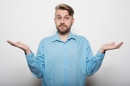 Can you believe it? Frustrated mature man in shirt looking at camera and gesturing while standing against white wall.