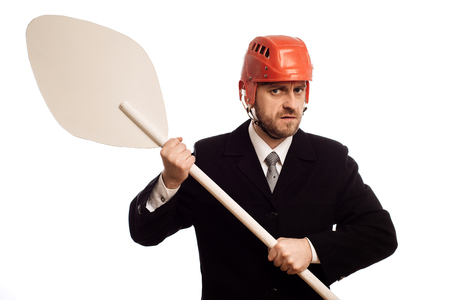 austere businessman in a helmet and with an oar in his hands on white background Stock Photo
