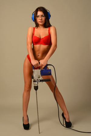 sexy brunette in red lingerie goggles and headphones worth holding perforator drill isolated on gray background Stock Photo