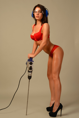 sexy brunette woman in red lingerie goggles and headphones worth holding perforator drill isolated on gray background