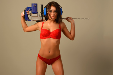 attractive, daring young woman in red in red lingerie goggles and headphones holds on her shoulder a punch drill