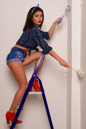 surprised young woman in a shirt and shorts paints a wall with two paintballs standing on a ladder Stock Photo
