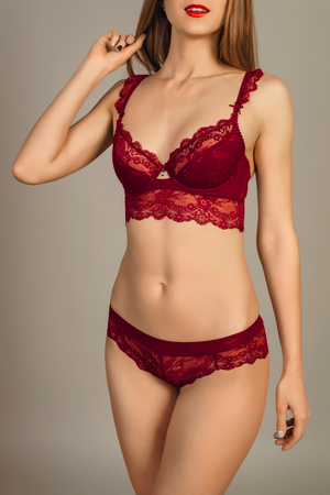 beautiful blonde girl in red lingerie posing on gray background. Close up.