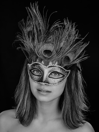 Black and white close-up portrait of a beautiful green-eyed woman in a Venetian carnival mask on a dark background. ring flash