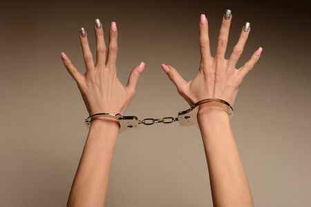 Victim of fashion. The concept. Beautiful female hands with manicure in handcuffs.