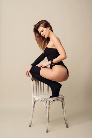 attractive young blond woman in black body and leggings sitting squatting her back on a white chair.