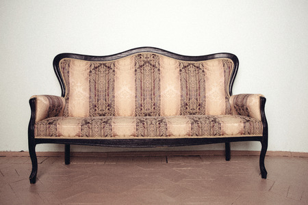 Luxurious antique velor sofa stands on a wooden floor near the wall Stock Photo
