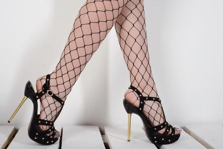 Piernas de mujer seductora con medias de red y tacones altos de pie sobre paletas de madera blanca
