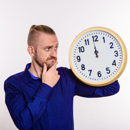 A stylish man thinks out the idea and holds a large wall clock on white background Stock Photo