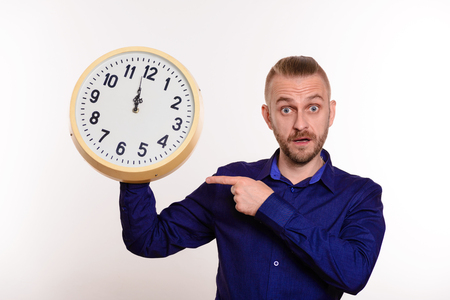 A stylish man holds a large wall clock in his hands and points to them with his finger on white background