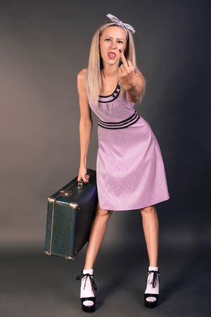 Slender young woman in a pink dress with a suitcase standing on a gray background and showing a fack sing 스톡 콘텐츠