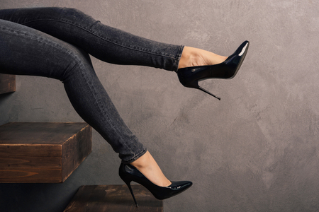 womens legs in jeans and high-heeled shoes on a wooden cantilever ladder.