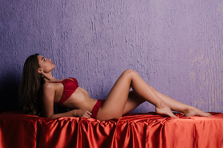 Sexy woman with a red lingerie lying on the sofa near the purple wall.